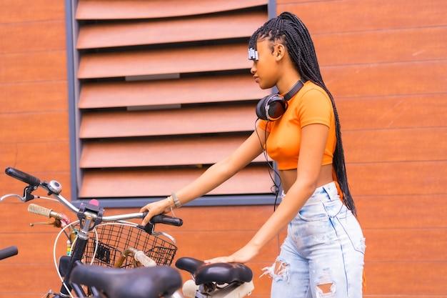 街で若いトラップダンサーとのライフスタイル。市内のオレンジ色のシャツを着たアフリカの民族グループの黒グラインドガール。市内に駐車した自転車のコーフィング