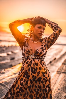 Lifestyle with sunset, a young woman in a long leopard dress on the beach of sakoneta in the village of deba, gipuzkoa. basque country. portrait of sexy girl with arms up by the sea
