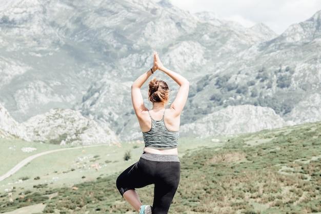 ライフスタイルの女性は健康的な生活のために運動とポーズをとります。若い女の子や人々は、自然の山の背景をトレーニングするためのバランスのとれた体の重要な禅と瞑想を提起します。バナー用のスペースをコピーします。