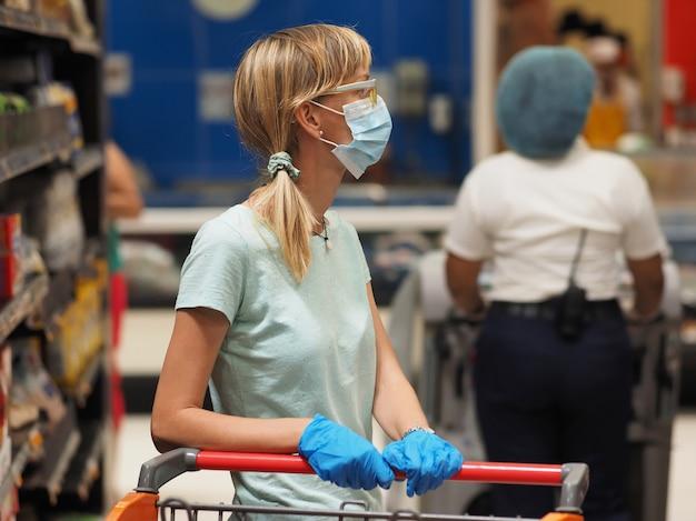 생활 양식. 상품 및 고객 선반 배경 슈퍼마켓에 식료품 카트 의료 마스크 및 라텍스 장갑을 착용하는 여자. 코로나 바이러스 covid-19로부터 보호.