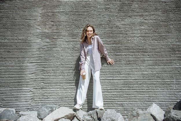 라이프 스타일 젊은 아름 다운 갈색 머리 모델 커피 한 잔과 함께 거리에서 벽에 포즈