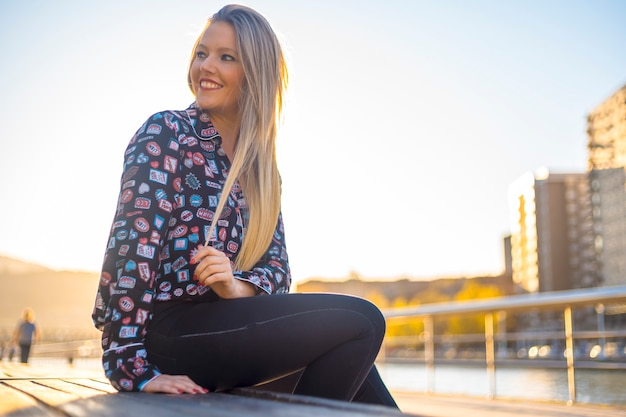 Lifestyle, a young blonde in the city of bilbao on the river promenade