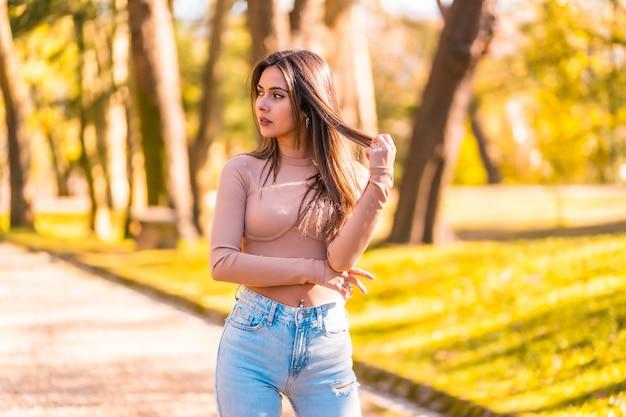 Образ жизни, молодая кавказская брюнетка в розовом свитере и джинсах гуляет в парке осенью