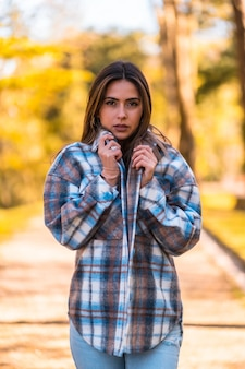 Образ жизни, молодая кавказская брюнетка в клетчатом шерстяном свитере и рваных джинсах гуляет в парке осенью