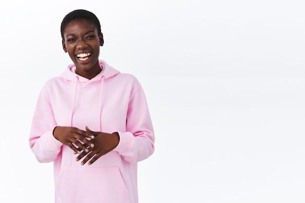 Образ жизни, молодое поколение и концепция женщин. беззаботная афро-американская девушка в розовой толстовке с капюшоном, держась за руки в расслабленной позе
