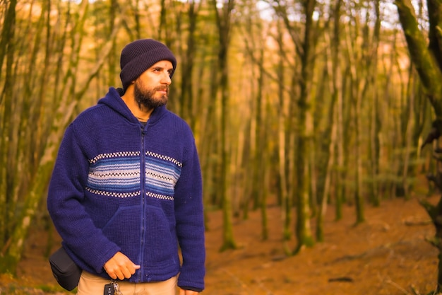 Lifestyle, a young man in a blue wool sweater and a hat enjoying the forest in autumn. artikutza forest in san sebastin, gipuzkoa, basque country. spain