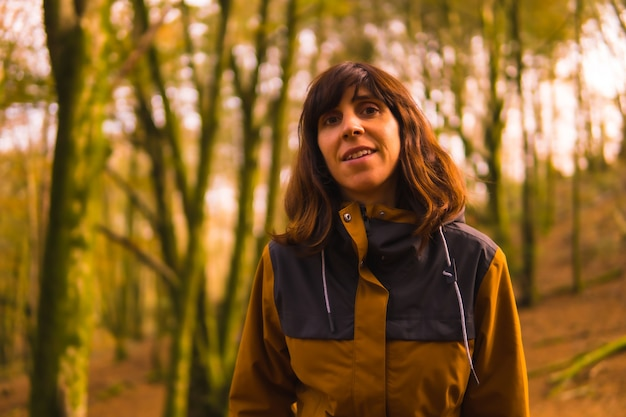 Lifestyle, a young woman in a yellow jacket walking in a forest in autumn. artikutza forest in san sebastin, gipuzkoa, basque country. spain