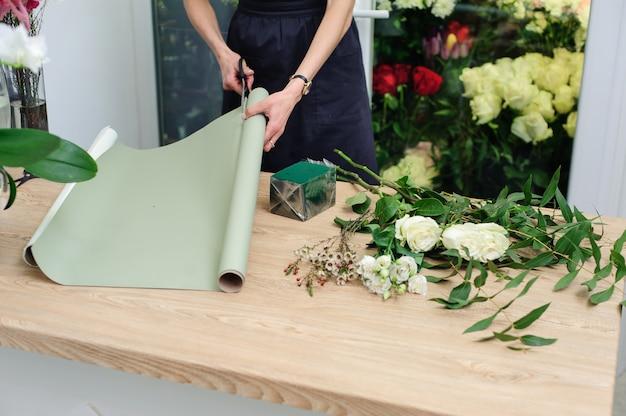 Садовник в цветочном магазине делает букет. lifestyle цветочный магазин. красивая цветочная композиция. деталь.