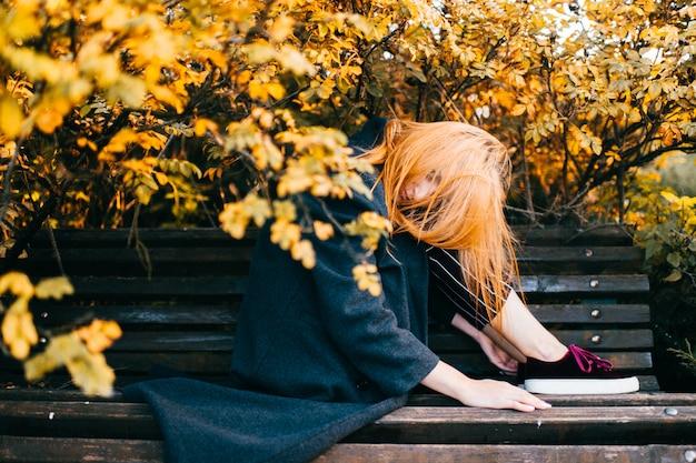犬バラの茂みの下のベンチに座っている若い美しい赤毛の女の子。かわいい女性lifestysleソフトフォーカスの肖像画。物思いに沈んだ青い目をした十代の屋外でポーズをとって思慮深い穏やかな顔。かわいいスタイリッシュな女性
