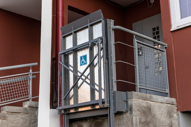 Lift for people with disabilities at the entrance to a residential apartment building. support for people moving in a wheelchair.