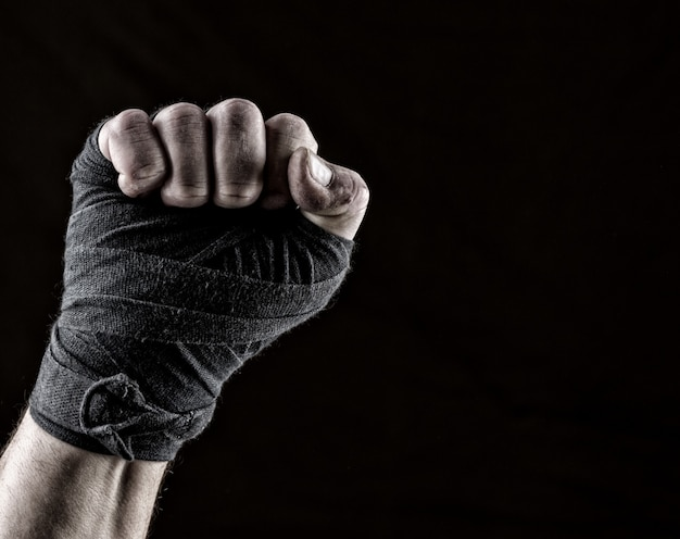 Lifted up fist of athlete wrapped in black textile bandage