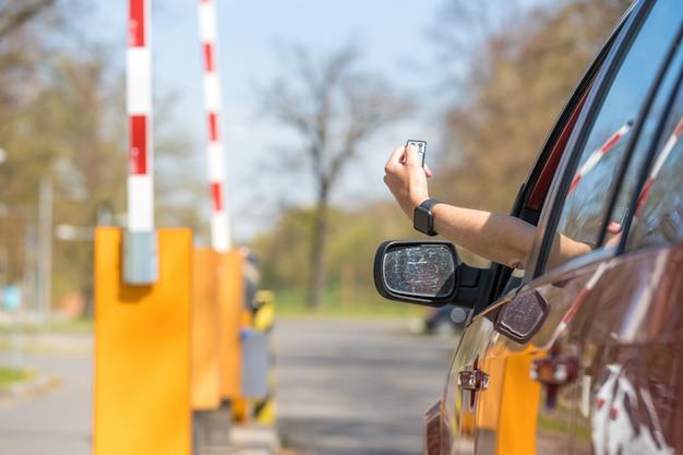 Подъемный барьер на въезде на парковку с помощью пульта дистанционного управления