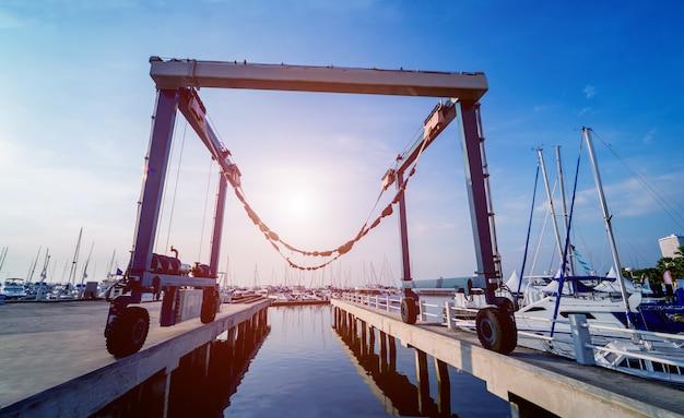 Lifting crane for elevating boat at harbor docks.