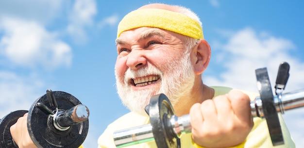 彼女のトレーニングの後にダンベルを持ち上げる老人シニアスポーツマンダンベルを持ち上げる老人のトレーニング