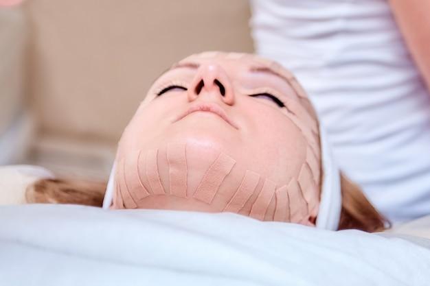 Поднятие кожи лица женщина с косметической процедурой тейпирования лица