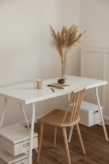 木製の椅子、テーブル、葦のパンパスグラスブーケ、マグカップ、ノートブックを備えた軽い美的ヒュッゲスペース。
