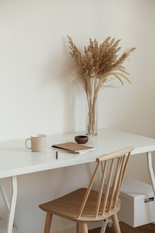 Light aesthetic hygge space with wooden chair, table, reed pampas grass bouquet, mug, notebook