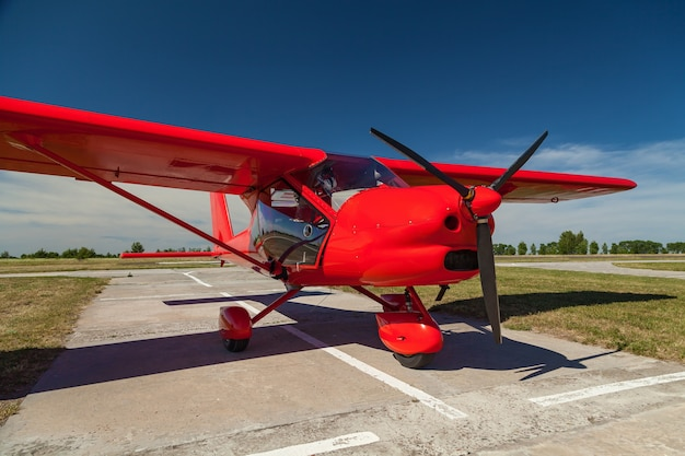Light aircraft of a red color on a private airfield to prepare for the flight