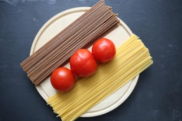 明るい面と暗い茶色のスパゲッティとトマト、黒い表面に丸い板 Premium写真