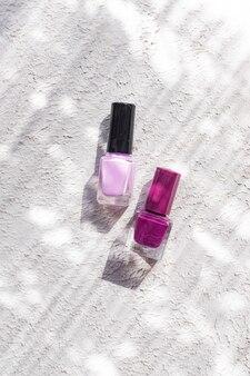 Светло-темно-розовые лаки для ногтей на белом бетонном фоне с естественным освещением