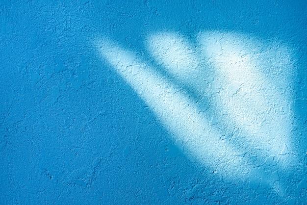 오래 된 벽의 빛과 그림자 질감. 초라한 파란색 페인트. 금이 콘크리트 빈티지 벽, 배경.