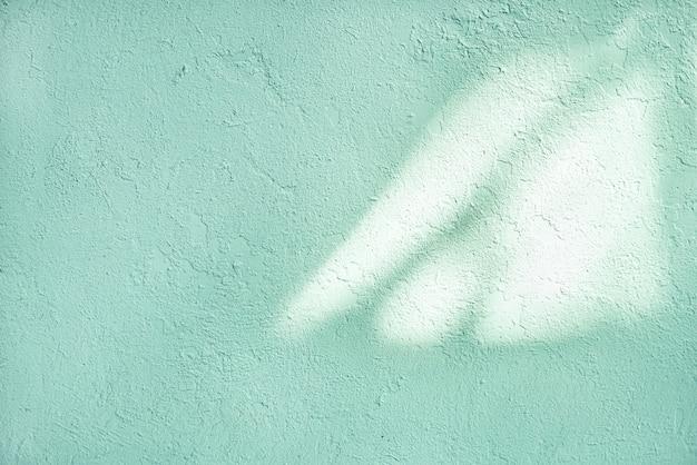 古い壁の光と影のテクスチャ。ぼろぼろ、緑の潮、青磁の緑のペンキ。ひびの入ったコンクリートのヴィンテージの壁、背景