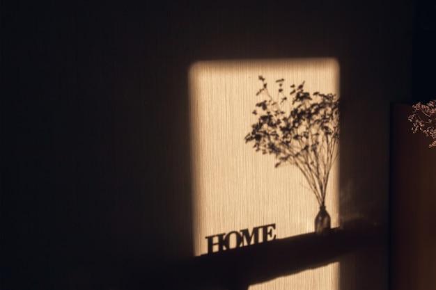 빛과 비문 벽에 창문을 통해 그림자 집과 투명 꽃병에 말린 된 꽃다발입니다.