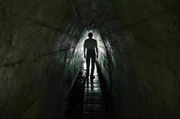 Свет в конце туннеля. узкий проход и мужик.