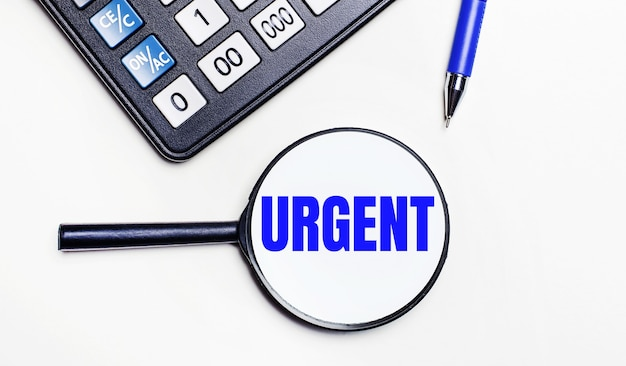 On a light background, a black calculator, a blue pen and a magnifying glass with text inside the word urgent. view from above