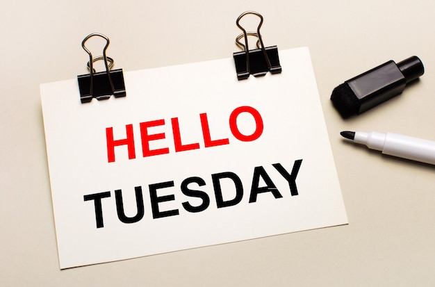 On a light background, a black open marker and on black clips a white sheet of paper with the text hello tuesday