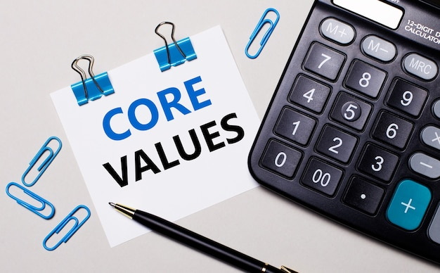 On a light background, a calculator, a pen, blue paper clips and a sheet of paper with the text core values