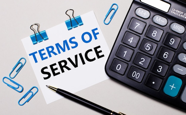 On a light background, a calculator, a pen, blue paper clips and a sheet of paper with the text terms of service. view from above