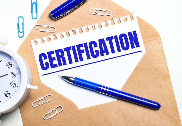 On a light background, a craft envelope, an alarm clock, paper clips, a blue pen and a sheet of paper with the text certification.