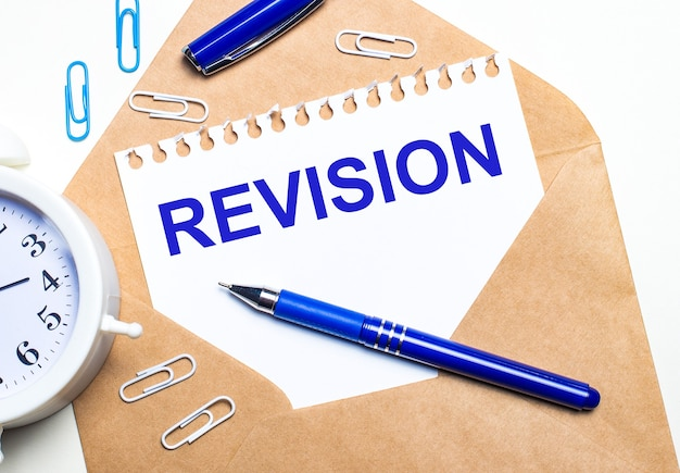 On a light background, a craft envelope, an alarm clock, paper clips, a blue pen and a sheet of paper with the text revision.