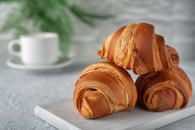 On a light background a freshly baked fragrant croissant with a cup of milk
