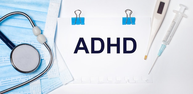 On a light background lie a stethoscope, an electronic thermometer, a syringe, a face mask and a sheet of paper with the text adhd. medical concept