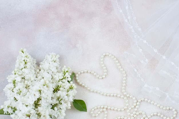 On a light background lies a veil, pearl beads and a bouquet of white lilac