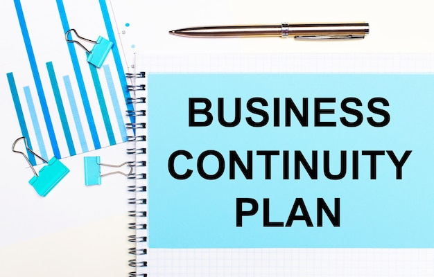 On a light background - light blue diagrams, paper clips and a sheet of paper with the text business continuity plan