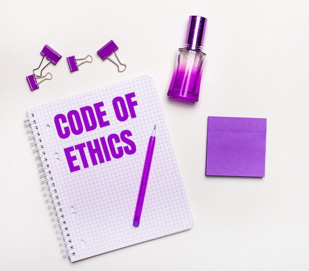 On a light background - a lilac gift, perfume, lilac business accessories and a notebook with a lilac inscription code of ethics.