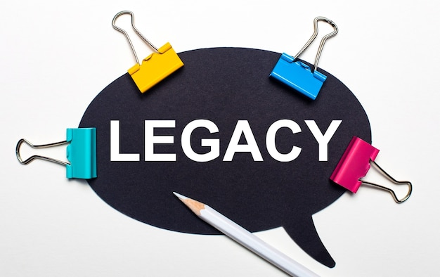 On a light background, multi-colored paper clips, a white pencil and black paper with the words legacy