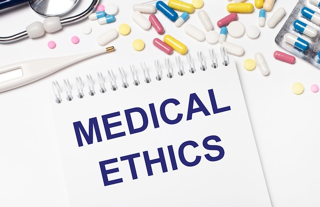 On a light background, multi-colored pills, a stethoscope, an electronic thermometer and a notebook with the text medical ethics. medical concept.