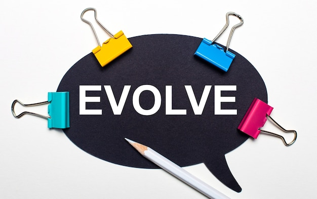 On a light background, multicolored paper clips, a white pencil and black paper with the words evolve