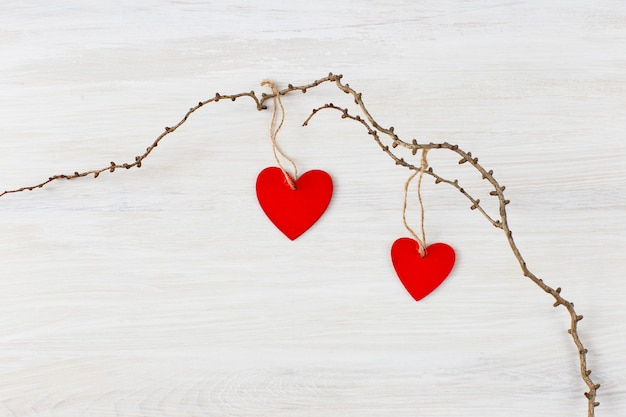 On a light background an old branch and on it are two red wooden hearts