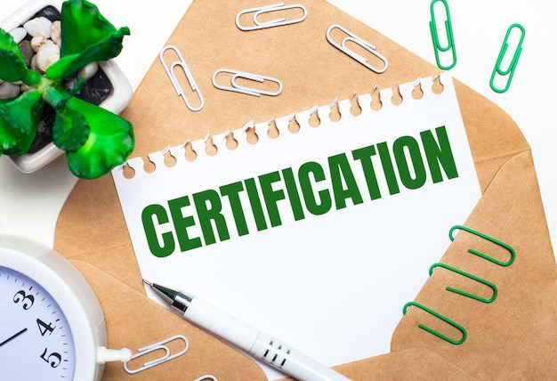 On a light background, an open envelope, a white alarm clock, a green plant, white and green paper clips, a white pen and a sheet of paper with the text certification