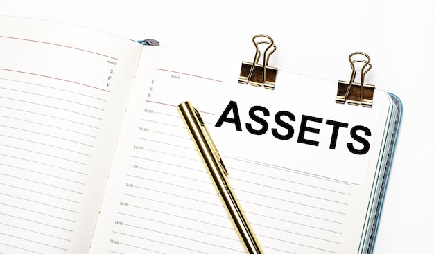 On a light background, an open notebook, a sheet of paper with gold clips and the text assets and a gold pen. view from above. business concept