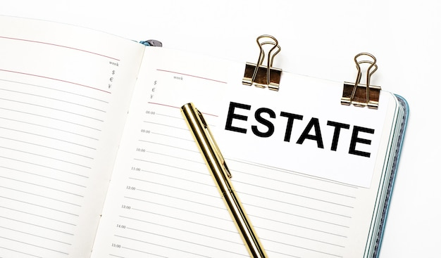 On a light background, an open notebook, a sheet of paper with gold clips and the text estate and a gold pen. view from above. business concept