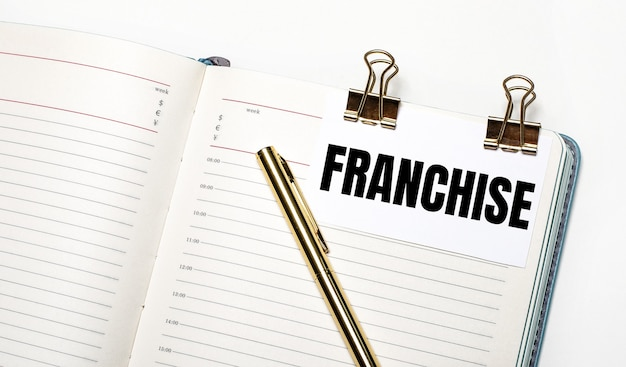 On a light background, an open notebook, a sheet of paper with gold clips and the text franchise and a gold pen. view from above. business concept