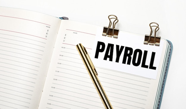 On a light background, an open notebook, a sheet of paper with gold clips and the text payroll and a gold pen. view from above. business concept