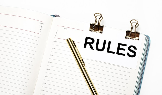 On a light background, an open notebook, a sheet of paper with gold clips and the text rules and a gold pen. view from above. business concept
