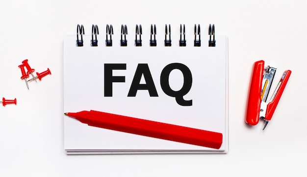 On a light background, a red pen, a red stapler, red paper clips and a notebook with the inscription faq